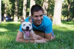 Muchacho joven que abraza su perro Fotos de archivo