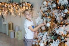 Muchacho joven que adorna el árbol de navidad Imagen de archivo