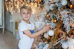 Muchacho joven que adorna el árbol de navidad Fotos de archivo
