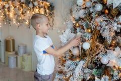 Muchacho joven que adorna el árbol de navidad Fotografía de archivo