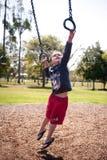 Muchacho joven que alcanza en barras de mono Fotos de archivo