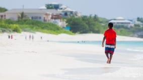 Muchacho joven que camina en la playa blanca tropical de la arena Fotografía de archivo libre de regalías