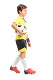 Muchacho joven que camina y que lleva a cabo un fútbol Fotografía de archivo libre de regalías