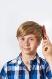 Muchacho joven que cepilla su pelo Imágenes de archivo libres de regalías