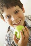 Muchacho joven que come Apple Imagenes de archivo