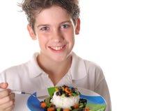 Muchacho joven que come el arroz, habas y los veggies sanos Foto de archivo libre de regalías