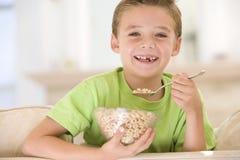 Muchacho joven que come el cereal en la sonrisa de la sala de estar Fotografía de archivo