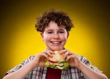 Muchacho joven que come el emparedado grande Imagen de archivo