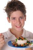 Muchacho joven que come el ver sano del arroz, de las habas y de los veggies Imágenes de archivo libres de regalías