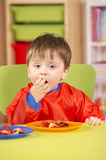 Muchacho joven que come la fruta en un cuarto del cuarto de niños foto de archivo