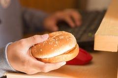 Muchacho joven que come la hamburguesa y que usa el ordenador Imagen de archivo libre de regalías