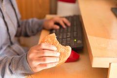 Muchacho joven que come la hamburguesa y que usa el ordenador Fotos de archivo