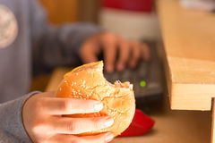 Muchacho joven que come la hamburguesa y que usa el ordenador Foto de archivo libre de regalías