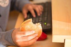 Muchacho joven que come la hamburguesa y que usa el ordenador Foto de archivo