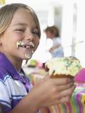 Muchacho joven que come la magdalena en la fiesta de cumpleaños Fotos de archivo libres de regalías