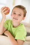 Muchacho joven que come la manzana en sala de estar Foto de archivo libre de regalías