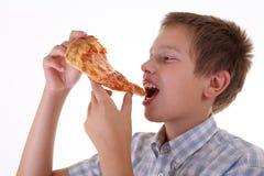 Muchacho joven que come la pizza Imagen de archivo libre de regalías
