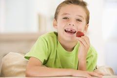 Muchacho joven que come las fresas en sala de estar Imagenes de archivo