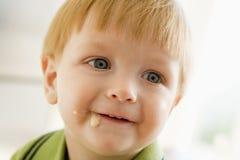 Muchacho joven que come los alimentos para niños con lío en cara Foto de archivo