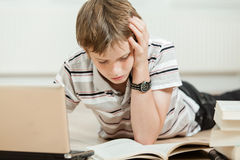 Muchacho joven que concentra en sus estudios en casa Fotos de archivo