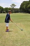 Muchacho joven que conduce una pelota de golf Fotografía de archivo libre de regalías
