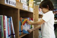 Muchacho joven que consigue a niños el libro de la historia de estante en biblioteca foto de archivo
