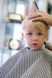 Muchacho joven que consigue un corte de pelo Fotos de archivo libres de regalías