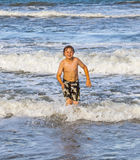 Muchacho joven que corre a través del agua en la playa Fotografía de archivo libre de regalías