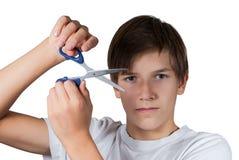 Muchacho joven que corta su pelo con las tijeras Imagen de archivo libre de regalías