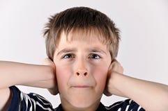 Muchacho joven que cubre sus oídos con las manos Imagenes de archivo