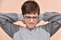 Muchacho joven que cubre sus oídos con las manos Fotografía de archivo