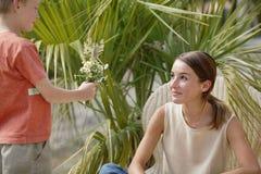Muchacho joven que da las flores a la mujer Fotos de archivo