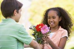 Muchacho joven que da las flores y la sonrisa de la chica joven Fotografía de archivo