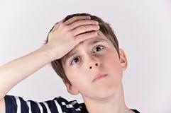 Muchacho joven que da una palmada a la mano en la cabeza Fotografía de archivo libre de regalías