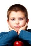 Muchacho joven que decide comer una manzana sana Fotos de archivo