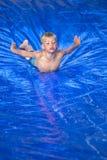Muchacho joven que desliza abajo un resbalón y una diapositiva al aire libre Imagen de archivo libre de regalías