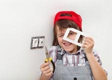 Muchacho joven que desmonta un accesorio eléctrico de la pared imagenes de archivo