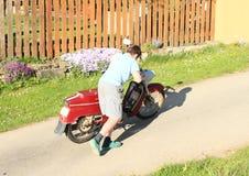 Muchacho joven que empuja en una moto Imágenes de archivo libres de regalías