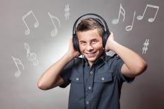 Muchacho joven que escucha una música y que canta Imagenes de archivo