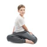 Muchacho joven que estira o que hace yoga Fotografía de archivo