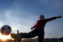 Muchacho joven que golpea la bola con el pie en la hierba al aire libre, aislado Fotos de archivo libres de regalías