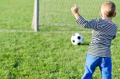 Muchacho joven que golpea un balón de fútbol con el pie imagen de archivo libre de regalías