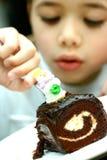Muchacho joven que goza de una torta Fotografía de archivo libre de regalías