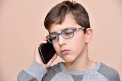 Muchacho joven que habla en su teléfono elegante Imagen de archivo libre de regalías