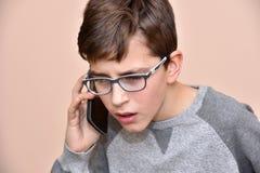 Muchacho joven que habla en su teléfono elegante Fotos de archivo