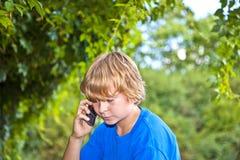 Muchacho joven que habla en un teléfono celular Imagen de archivo