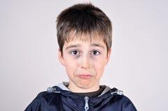 Muchacho joven que hace una cara divertida Foto de archivo