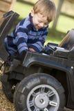 Muchacho joven que juega al aire libre con la sonrisa del carro del juguete Imágenes de archivo libres de regalías
