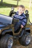 Muchacho joven que juega al aire libre en la sonrisa del carro del juguete Fotos de archivo