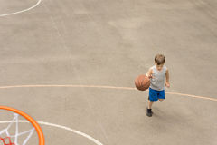 Muchacho joven que juega al baloncesto que corre con la bola Foto de archivo libre de regalías